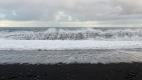 La mer fait de la dentelle sur le sable noir