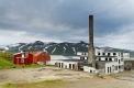 Une maison rouge et une cheminée d'usine